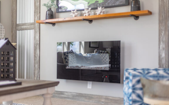 Electric fireplace in The Cottage Farmhouse by Palm Harbor Homes. 2 bedrooms 2 bathrooms. 1,387 square feet with built in porch. Only available in Florida. LS28522J