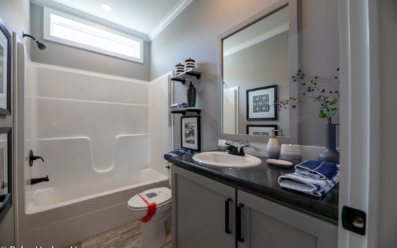 Second or guest bath in The Cottage Farmhouse by Palm Harbor Homes. 2 bedrooms 2 bathrooms. 1,387 square feet with built in porch. Only available in Florida. LS28522J